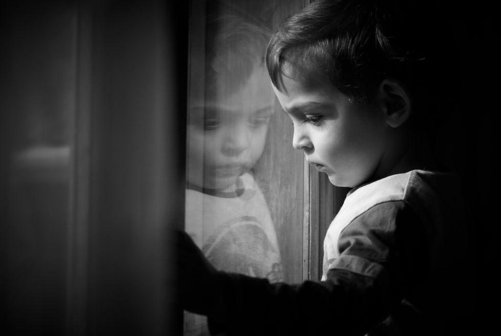 sad boy looking through window