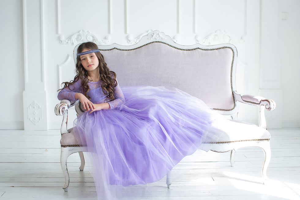 little girl in purple princess dress lying on white sofa