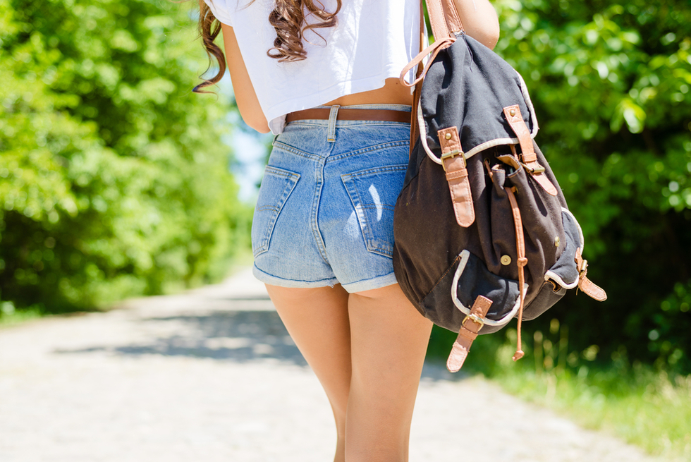 teenage girl in short shorts walking along roadside