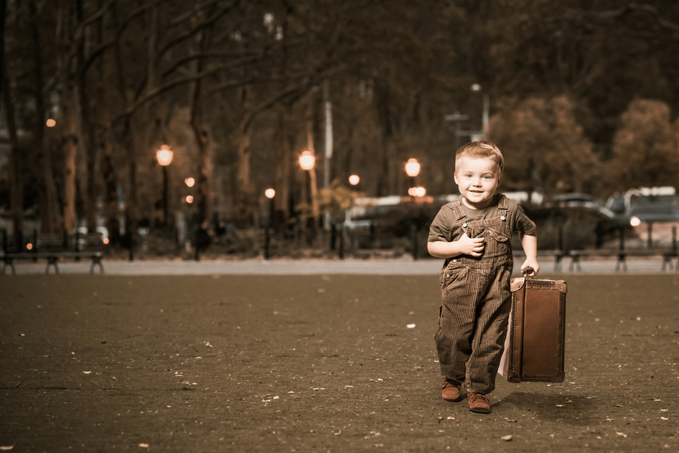 young boy with suitcase running away from home at night