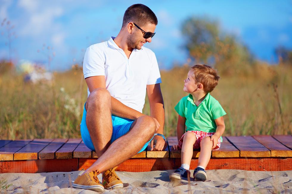 man in shorts talking to little boy near the seaside