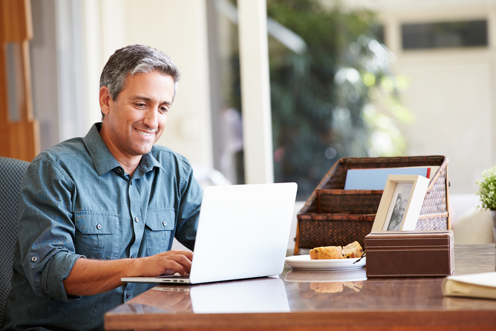 mature man smiling as he uses his laptop