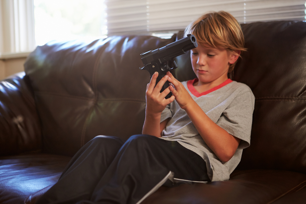 boy on sofa holding gun