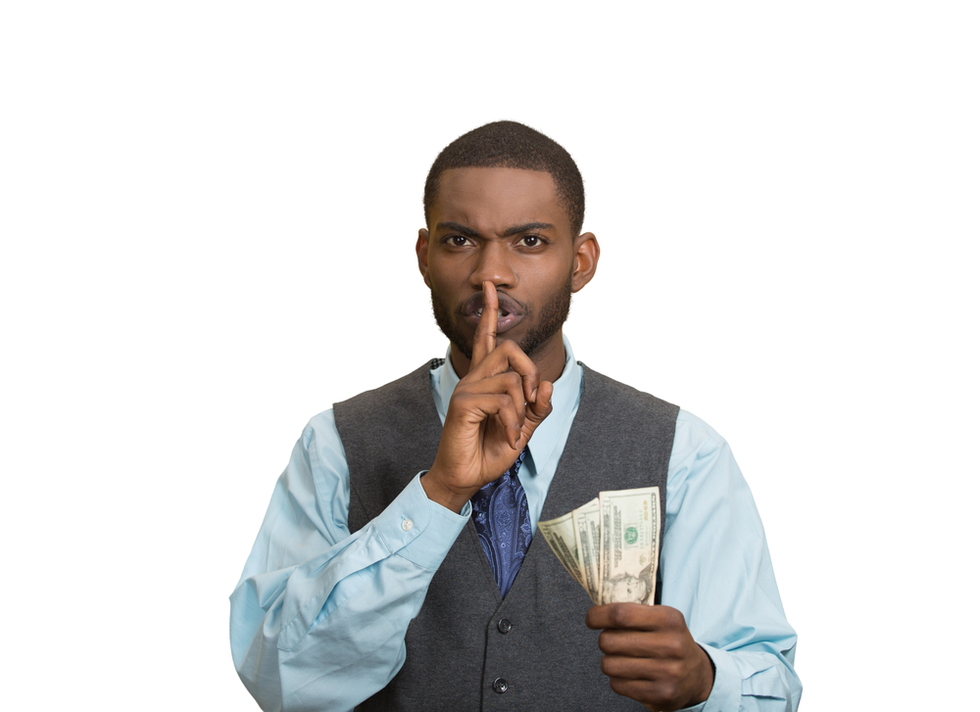 Young professional-looking African American man holding finger to his lips and money in his other hand