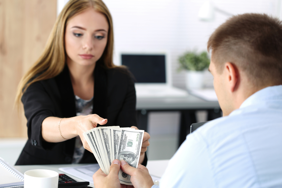 man giving young woman a large cash payment in an office