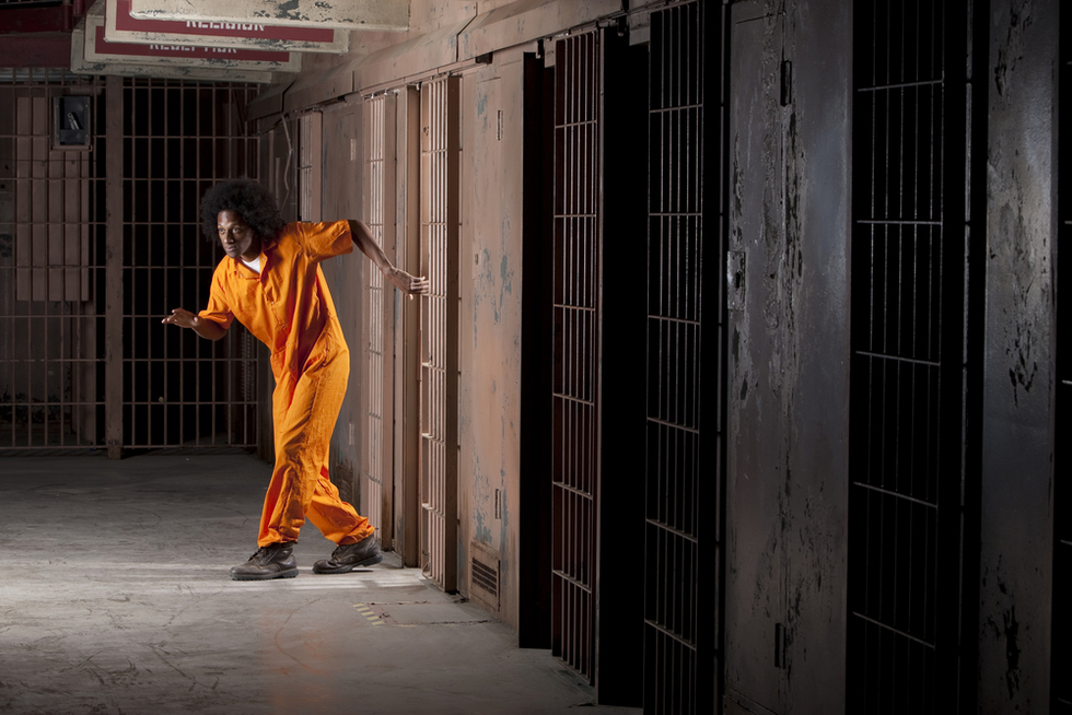 African American man leaving prison cell in his orange jumpsuit