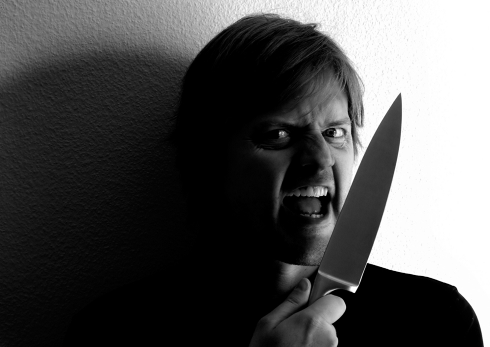 scary man holding a knife and looking crazy