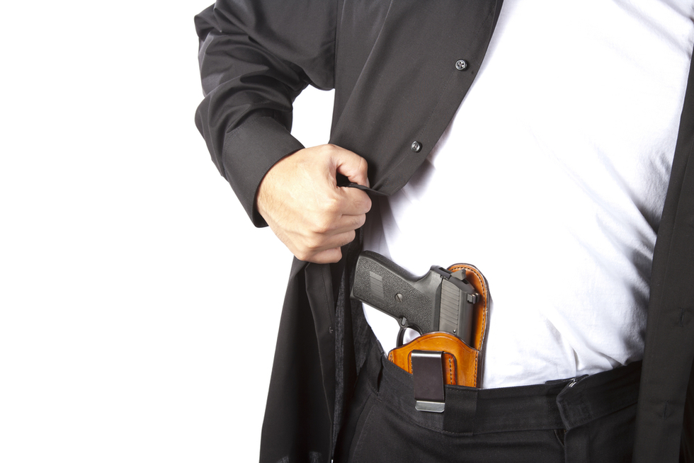 man opening jacket to reveal concealed handgun in holster
