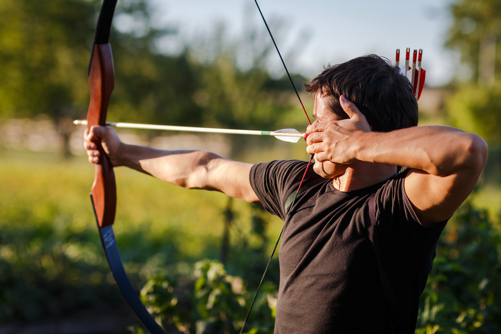 man shooting an arrow from a bow in the countryside