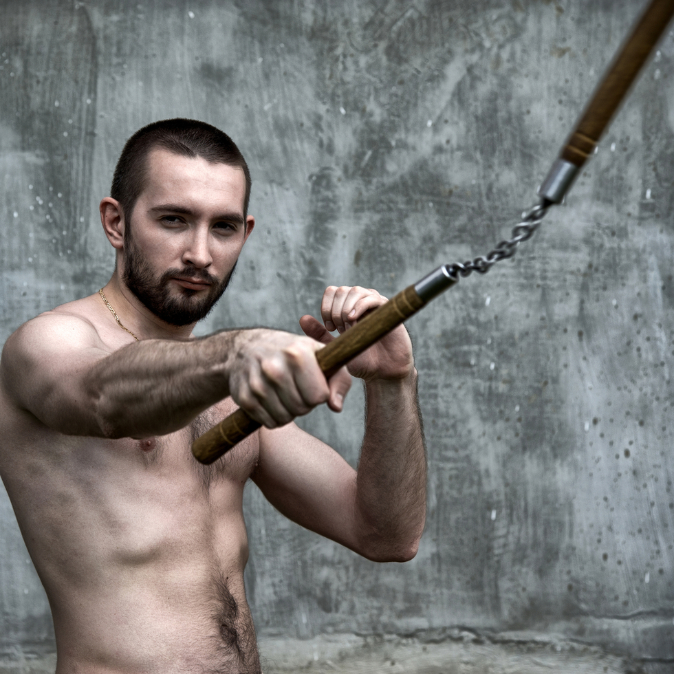 shirtless man swinging nunchaku in front of concrete wall