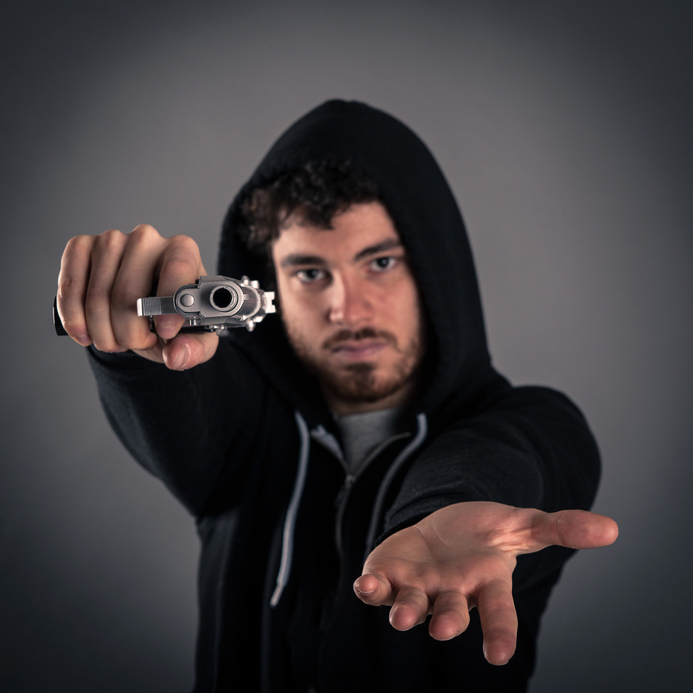 young man in hoodie pointing gun