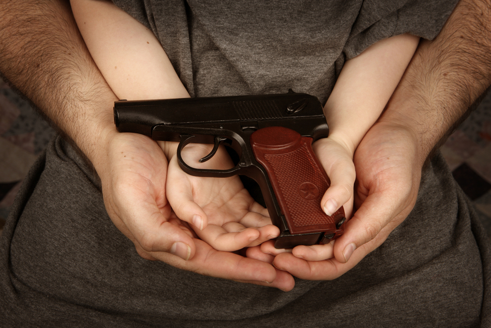 adult hands cradling the hands of a child holding a handgun