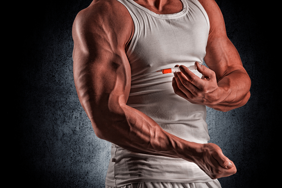 muscular man injecting anabolic steroids into his bicep