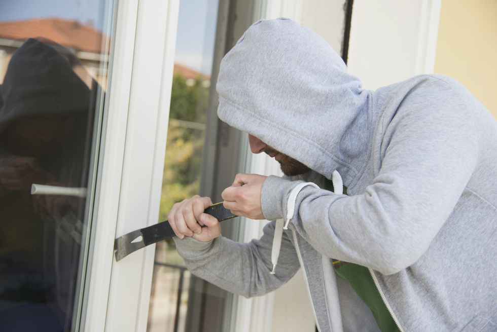 man in gray hoodie breaking into French door with crowbar