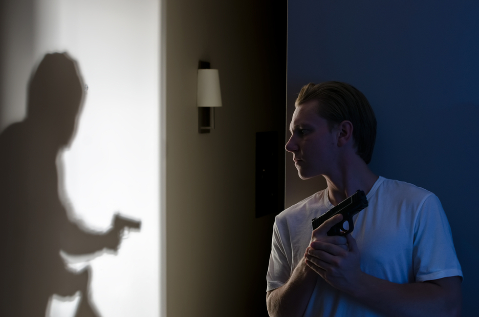 man in white t-shirt holding a gun while he looks at shadow of man with a gun in his house