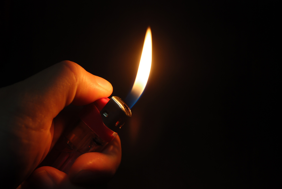 Hand holding flaming cigarette lighter against dark background