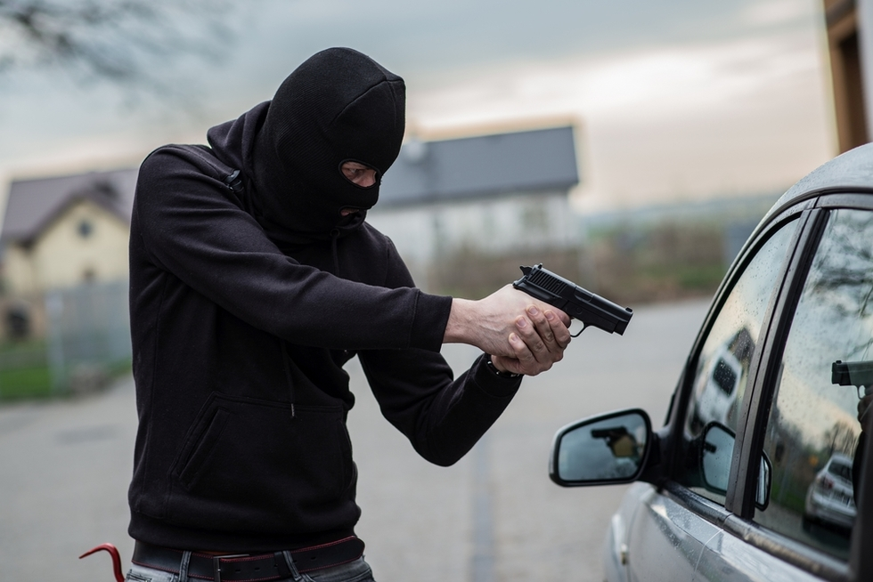 man in black hoodie pointing handgun at a car's driver