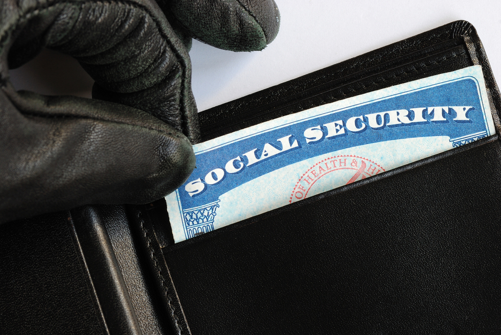 black-gloved fingers taking social security card out of someone's wallet