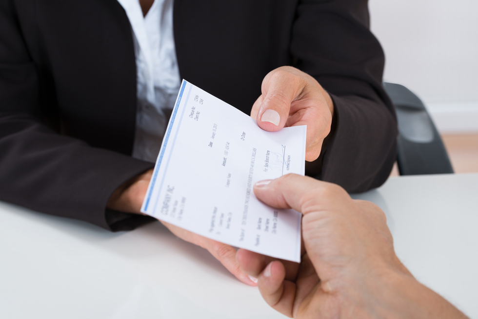 man in business suit handing someone a check