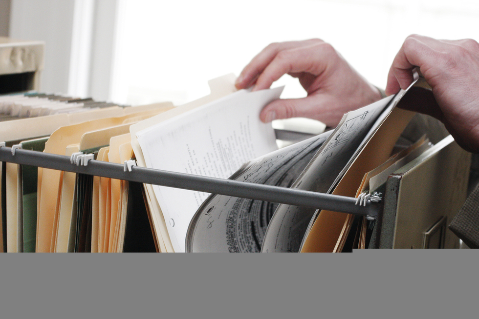 hands taking file from filing cabinet