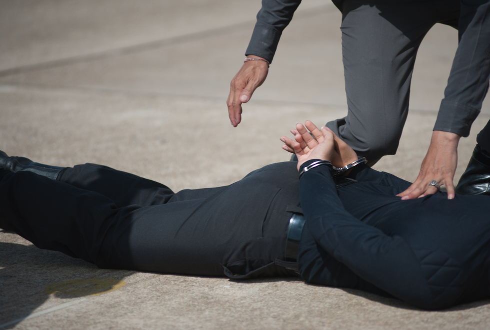 man lying on ground handcuffed by police