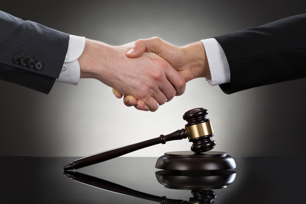 hands of men in suits shaking hands over gavel