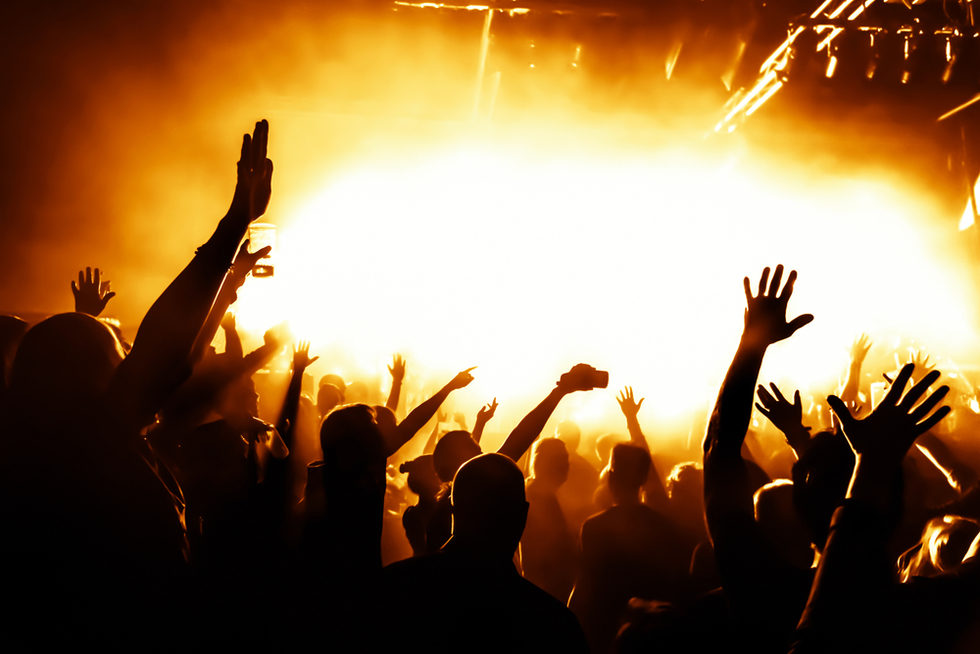 people partying at a nightclub with bright yellow light in the background