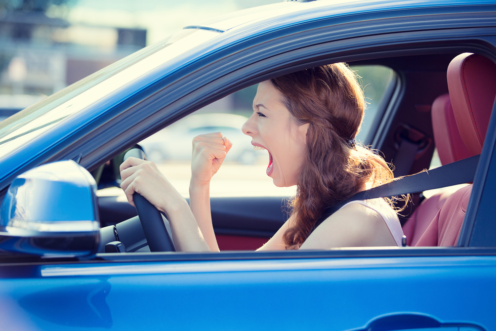 Red-haired woman in blue car screaming in frustration with one fist raised