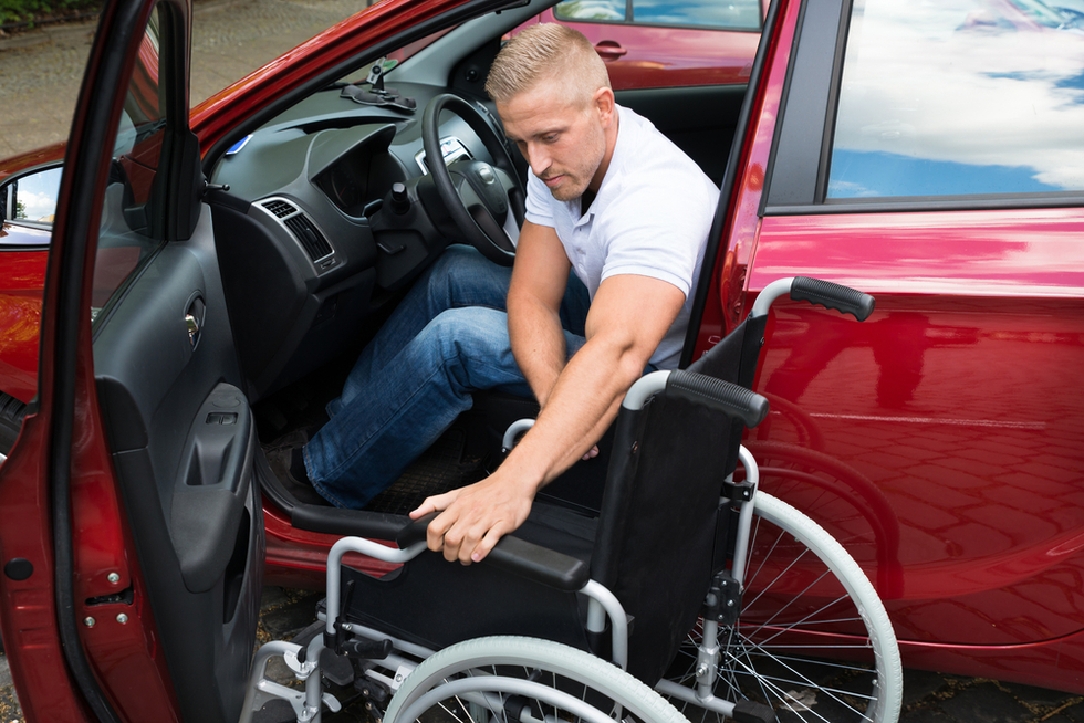 disabled male driver getting behind wheel of car from wheelchair