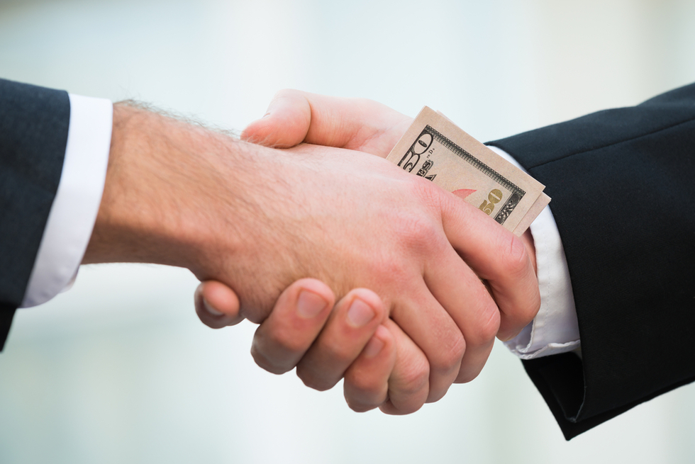 two men shaking hands with money in palms
