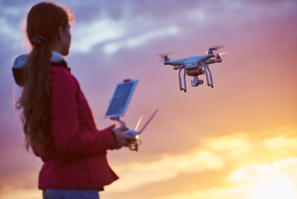girl flying unmanned drone at sunset