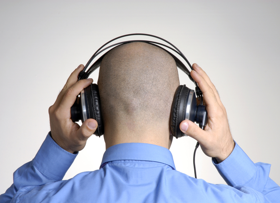 rear shot of bald man in blue shirt listening on over-the-ear headphones