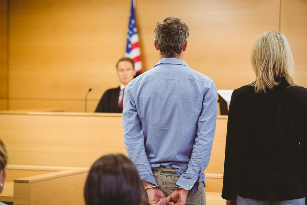 handcuffed male criminal defendant in court with female attorney and male judge