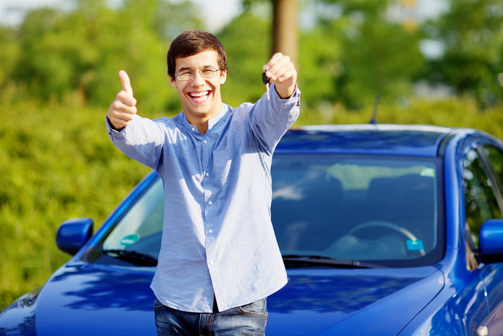 young man holding up keys, giving thumbs up, and smiling in front of blue car