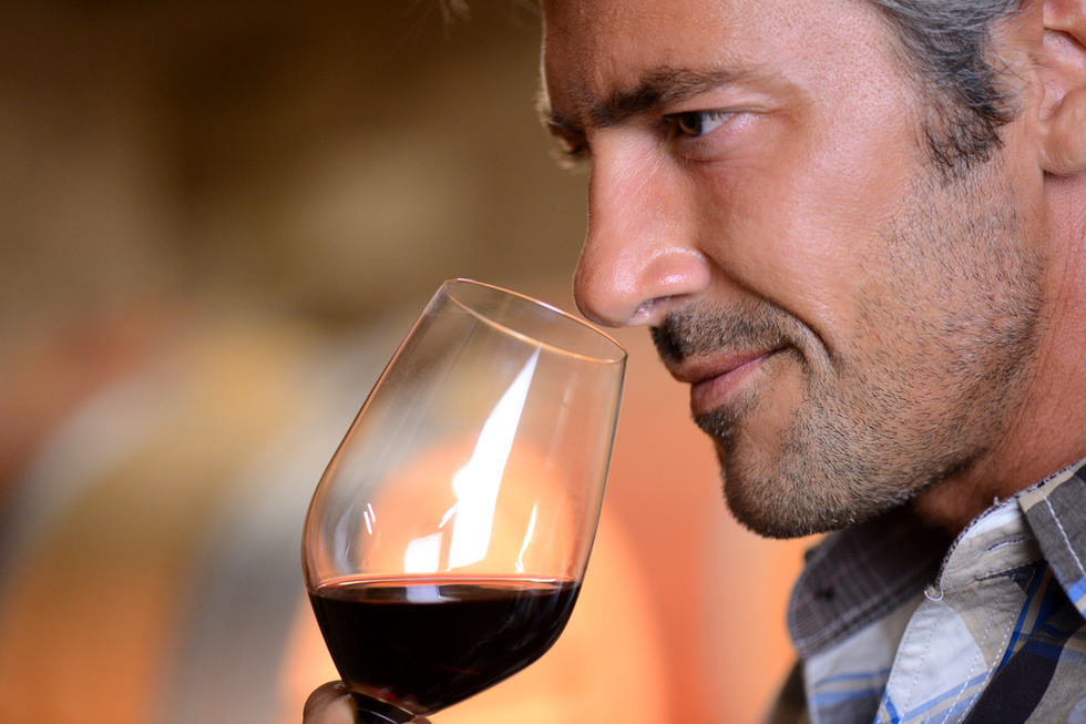 man sniffing a glass of red wine