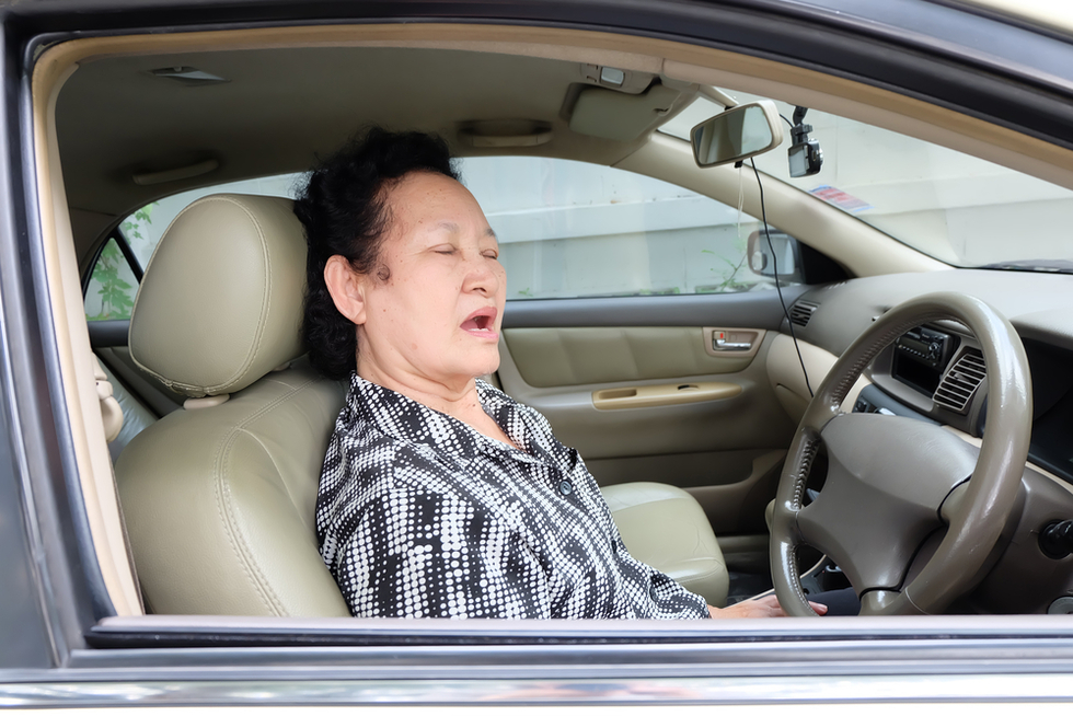 older woman asleep in the driver's seat of car