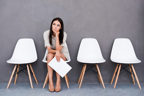 dejected looking young woman waiting for job interview with application in hand