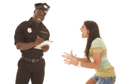 young woman yelling at smiling police officer who is writing her a ticket