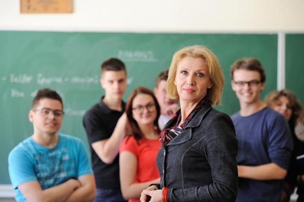 female teacher in front of students and blackboard