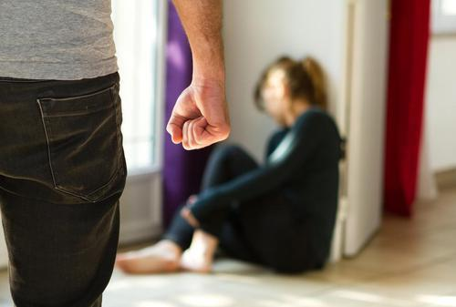 woman cowering on floor as man stands over her with raised fist