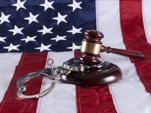 gavel and handcuffs on U.S. flag