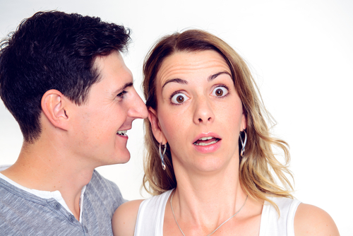 man whispering into ear of woman who has shocked expression on her face