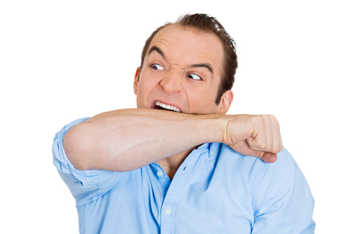 angry man biting his raised forearm