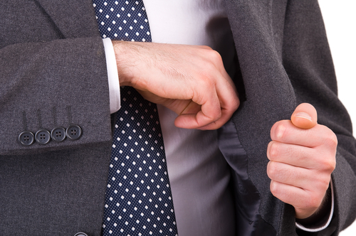 businessman putting something in his inside jacket pocket