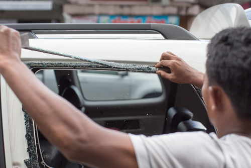 young man removing windshield from car