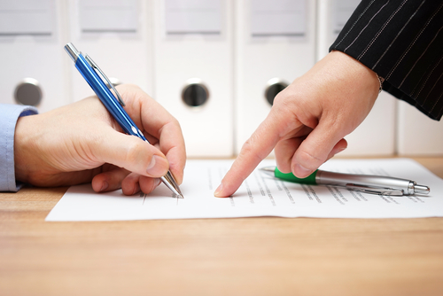 man's hand signing an agreement as another man in suit points where  to sign