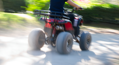 All terrain vehicle moving on dirt road