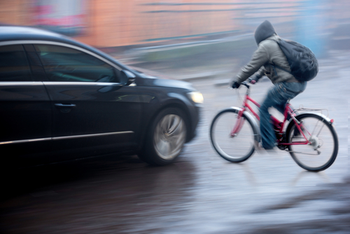 car about to hit young man in hoodie on bicycle