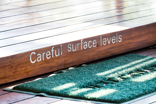 """Elevated wooden step painted with letters saying """"careful surface levels)"""