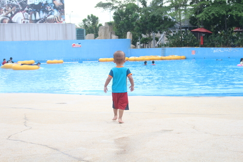 small boy walking alone toward public swimming pool